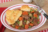 foto of biscuits gravy  - Beef stew with carrots peas and biscuits on a plate - JPG