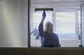 pic of detergent  - Woman at work professional female cleaner cleaning and wiping window in office with detergent