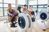 People working out on row machines in fitness studio