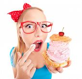 stock photo of pie-in-face  - Funny girl eating a cream puff - JPG