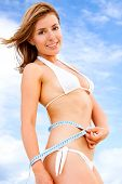 stock photo of woman bikini  - fit female measuring her waist  - JPG