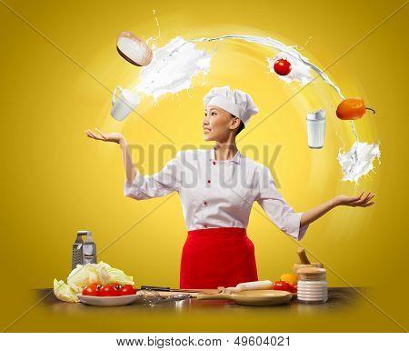 malabarista asiático femenino cocinar contra fondo de color