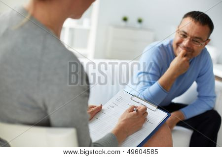 Female psychologist consulting mature man during psychological therapy session