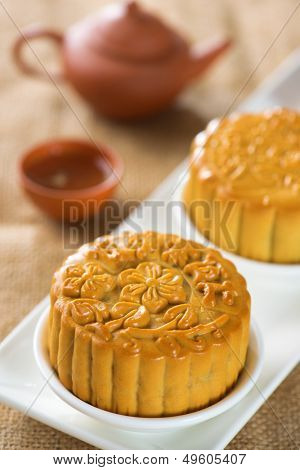 Chinese mid autumn festival foods. Traditional mooncakes on table setting with teapot.  The Chinese words on the mooncakes means assorted fruits nuts, not a logo or trademark.