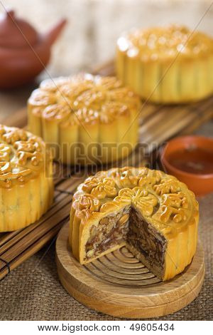 Chinese mid autumn festival foods. Traditional mooncakes on table setting with tea set.  The Chinese words on the mooncakes means assorted fruits nuts, not a logo or trademark.