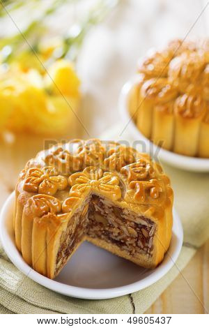 Sweet traditional mooncakes on table setting.  Chinese mid autumn festival foods. The Chinese words on the mooncakes means assorted fruits nuts, not a logo or trademark.