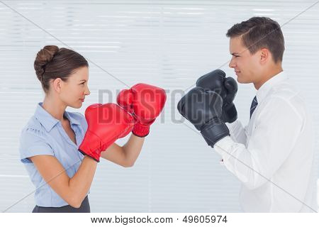 Colleagues in competition having a boxing match in bright office