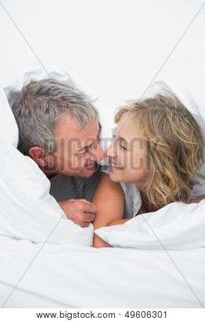 Cute middle aged couple under the duvet in bedroom at home