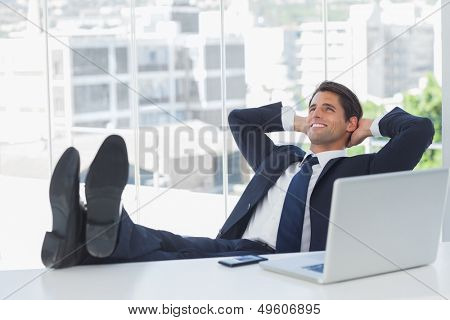Successful businessman in his office relaxing with his feet on his desk