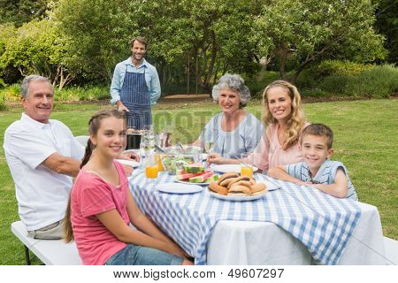 Happy extended family having a barbecue being cooked by father looking at camera
