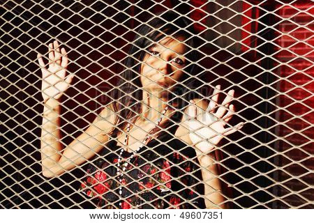 Young woman behind a metal fence