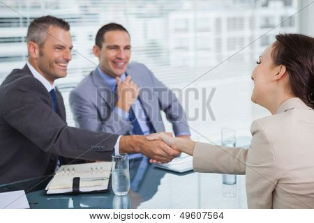 Cheerful young woman shaking hands with her future employer in bright office