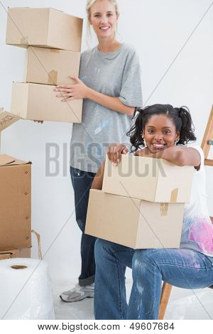 Happy housemates carrying cardboard moving boxes and smiling at camera in new home