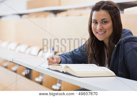 Girl sitting smiling while reading a book and taking notes at the lecture hall