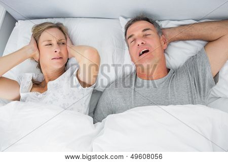 Annoyed wife blocking her ears from noise of husband snoring in bedroom at home
