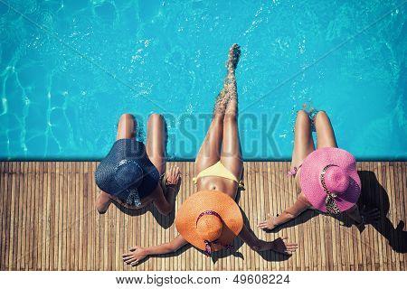 Three women in bikini wearing a straw hat by the swimming pool