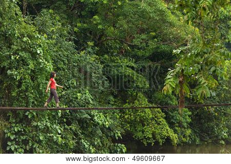 Woman walking on wooden suspended bridge in jungle, Thailand