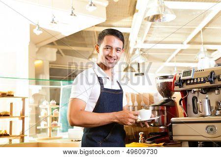 Coffeeshop - barista asiático apresenta café em sua loja