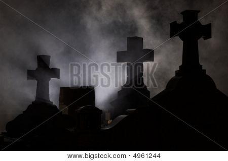 Lápide Cruz no cemitério à noite.