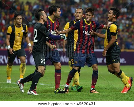 KUALA LUMPUR - AUGUST 10: FC Barcelona's players (maroon/blue) and Malaysia's players (yellow) fights in the game at the Shah Alam Stadium on August 10, 2013 in Malaysia. Barcelona wins 3-1.