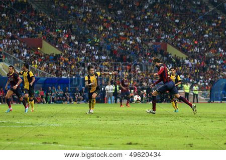 KUALA LUMPUR - AUGUST 10: FC Barcelona's Gerard Pique (maroon/blue) scores in a match vs Malaysia at the Shah Alam Stadium on August 10, 2013 in Kuala Lumpur, Malaysia. Barcelona wins 3-1.