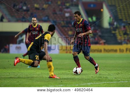 KUALA LUMPUR - AUGUST 10: Barcelona's Adriano (maroon/blue) dribbles past Malaysia's defenders (yellow/black) in a game at the Shah Alam Stadium on August 10, 2013 in Malaysia. Barcelona wins 3-1.