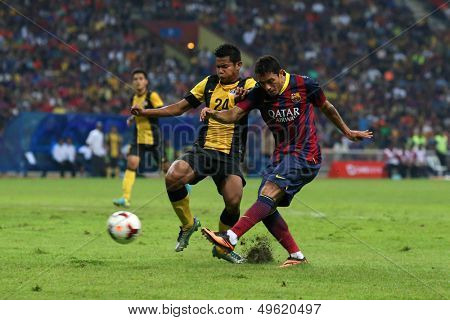 KUALA LUMPUR - AUGUST 10: Malaysia's N.M Shahrul (24) blocks a shot by Barcelona's Adriano (maroon/blue) in a friendly match at the Shah Alam Stadium on Aug 10, 2013 in Malaysia. Barcelona wins 3-1.