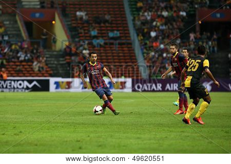 KUALA LUMPUR - AUGUST 10: FC Barcelona's Xavi Hernandez (maroon/blue) controls the midfield in a game vs Malaysia at the Shah Alam Stadium on August 10, 2013 in Malaysia. FC Barcelona wins 3-1.