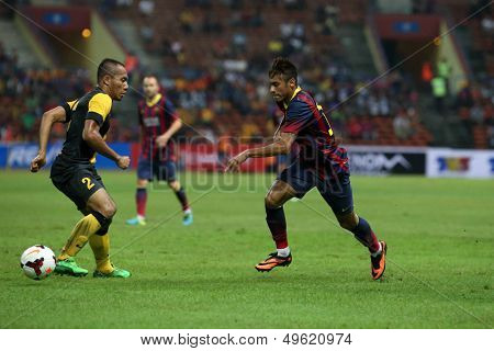 KUALA LUMPUR - AUGUST 10: Malaysia's Mahalli (2) defends against FC Barcelona's Neymar (maroon/blue) attack in a game at the Shah Alam Stadium on Aug 10, 2013 in Malaysia. FC Barcelona wins 3-1.