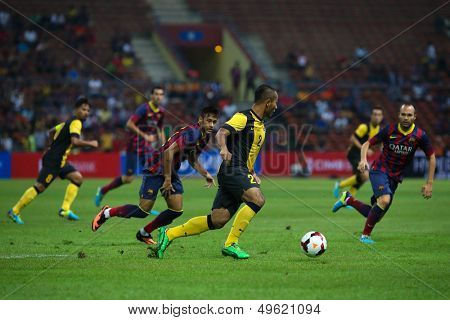 KUALA LUMPUR - AUGUST 10: Malaysia's Mahalli (2) controls the ball watched by Barcelona's Iniesta (right) in game played at the Shah Alam Stadium on August 10, 2013 in Malaysia. FC Barcelona wins 3-1.