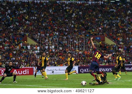 KUALA LUMPUR - AUGUST 10: Barcelona's Jordi Alba (18) is tackled by Malaysia's Aidil Zafuan (fallen) in match at the Shah Alam National Stadium on August 10, 2013 in Malaysia. FC Barcelona wins 3-1.