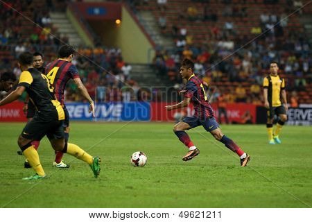 KUALA LUMPUR - AUGUST 10: FC Barcelona's Neymar (maroon/blue) leads in attack against the Malaysian team at the Shah Alam Stadium on August 10, 2013 in Malaysia. FC Barcelona wins 3-1.