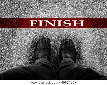 Finish line with businessman wearing dress shoes as metaphor for finishing work as a winner