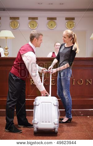 MOSCOW - MAY 22: Receptionist takes bag from guest in Bogorodino hotel, on May 22, 2013 in Moscow, Russia. Four-star Borodino hotel was built in 2007.