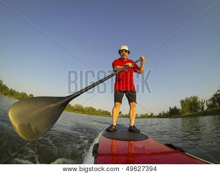 mature male paddler enjoying workout on stand up paddleboard (SUP), calm lake in Colorado, summer, distorted wide angle view