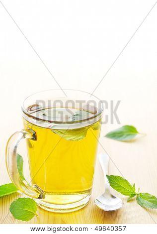 Mug of peppermint tea with fresh mint leaves
