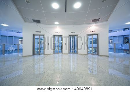 Four transparent elevator door in the business building with marble floor