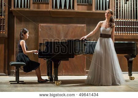 Woman pianist plays the piano and beautiful singer stands next
