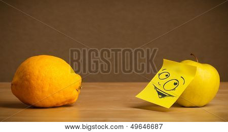 Apple with sticky post-it note reacting at lemon