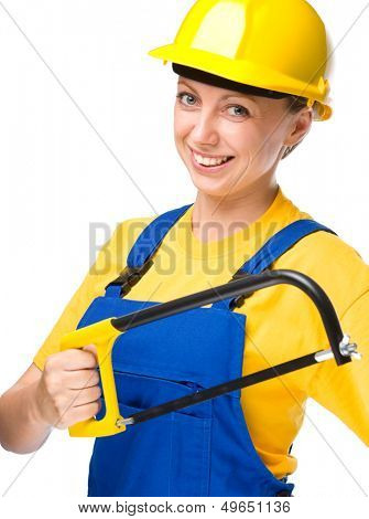 Young happy lady as a construction worker with hacksaw, isolated over white