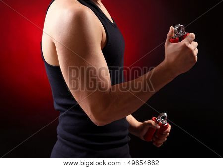 Handsome young muscular sportsman with expanders, on dark background