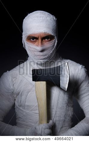 Mummy with axe in halloween concept