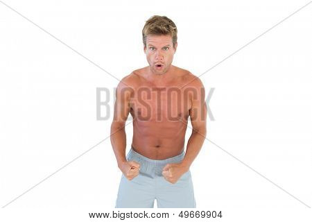 Shirtless serious man showing his muscles on white background