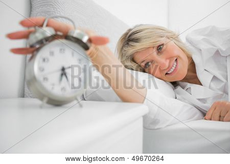 Blonde woman turning off ringing alarm clock lying in bed at home