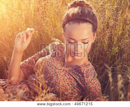 Beauty Romantic Girl Outdoors. Beautiful Teenage Model girl Lying on the Field in Sun Light. Autumn. Glow Sun, Sunshine. Backlit. Toned in warm colors