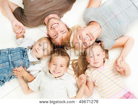Happy Big Family Portrait. Father, Mother, Daughter and Sons Together Lying on floor and Holding Hands on White Background. Smiling Parents with Little Kids. Studio Shot