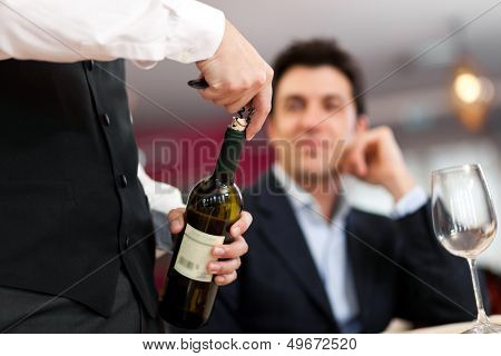 Waiter serving wine to a customer at the restaurant