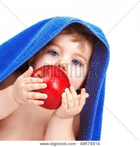 Closeup portrait of adorable toddler wrapped in blue towel, isolated on white background, baby boy biting red apple, infant after bath, healthy kids food