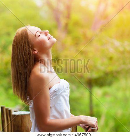 Closeup on beautiful calm woman enjoying nature on terrace in luxury cottage, spa resort, zen balance, summer vacation, harmony conception