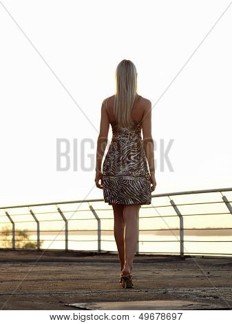 Blond Lady Walking Over Promenade